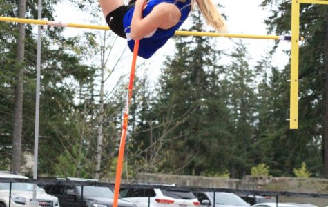 This season, a pole vaulter springs into action at a Track and Field meet, representing Tahoma High School against another school, seen here jumping over the bar.